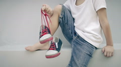 Little boy sitting near the house and keeping the youth sneakers in his hands Stock Footage