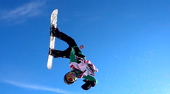 Snowboarder jumping against blue sky. Stock Footage