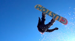 SLOW MOTION CLOSE UP: Snowboarder jumping over the camera spinning. Stock Footage