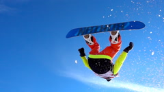 SLOW MOTION CLOSE UP: Snowboarder makes the rotation in the air over the camera. Stock Footage
