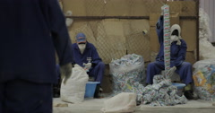 Unidentified Male Workers Organize Detergent Plastic Bags (4K) - stock footage