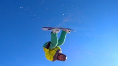 Snowboarder performs trick over the sunny blue sky. Stock Footage