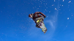 Snowboarder jumping high in snowpark on a beautiful sunny day. Stock Footage