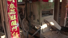 Medium shot old fashioned rice husker with Chinese banner in Asia Stock Footage