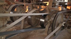 Medium shot 4 large pulleys with fabric belts in Asian factory - stock footage