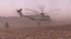War in Afghanistan - Marine helicopter taking off kicks up dust in desert Stock Footage