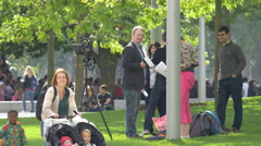 Tourists and journalists relaxing in the park in London Stock Footage