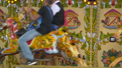 Kids having fun on a colorful marry-go-round in the park in London Stock Footage