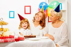 Little girl with mother and granny on birthday Stock Photos