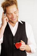 Smiling man holding heart shaped keyring - stock photo