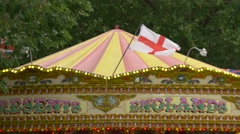 Carousel with flags rotating in a park in London Stock Footage