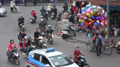 Poverty and inequality in Asia, balloon vendor at busy intersection in Vietnam Stock Footage
