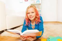 Blondie early teen girl read book at home Stock Photos