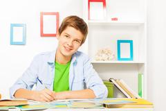 Smart boy with books and textbooks on the table - stock photo