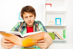 Clever boy read book sitting by table do homework Stock Photos