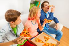 Happy teens eating pizza pieces together at home - stock photo