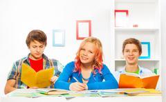 Boys and girl do homework together at home Stock Photos