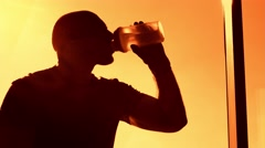 Man drinking water near the window at the sunset Stock Footage