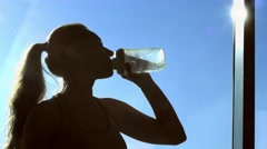Fitness girl drinking water near the window Stock Footage