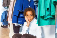 African boy with hand on cheek bored in shop - stock photo