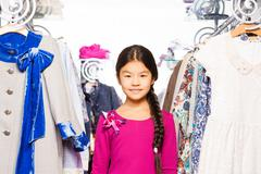 Small Asian girl with braid stands between clothes - stock photo