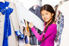 Asian girl with braid between clothes on  hangers - stock photo