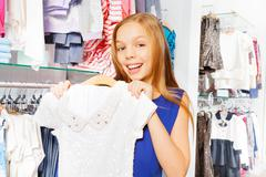 Happy girl with long hair holds dress on hanger Stock Photos