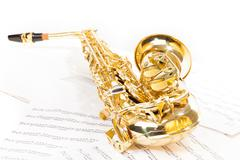 Alto saxophone laying on the musical notes Stock Photos
