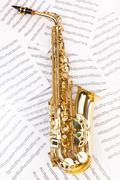 Shiny alto saxophone in full size on musical notes - stock photo