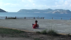 Zoom in child alone sitting on cement site Stock Footage