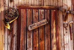 Gone fishing sign on old door - stock photo