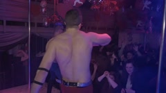 Back side topless boys in blue, red pants dance go go in nightclub. Slow motion - stock footage
