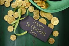 Happy St Patricks Day leprechaun hat with gold chocolate coins on vintage sty - stock photo