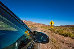 Car stopped on the road with arrow yellow sign Stock Photos