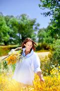 The girl holds a bouquet of wild flowers in hand. Stock Photos