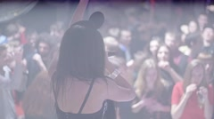 Back side MC girl in mouse ears, raise hand in nightclub. Slow motion. People - stock footage