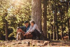 Mature couple under a tree with backpacks and compass - stock photo