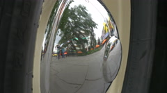 Street with people reflecting in the car hubcap, London - stock footage