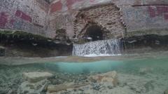 Underwater split: waterfall flowing from destroyed house. Stock Footage