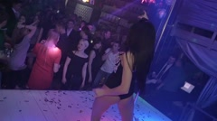 Back side MC girl in mouse ears wave hips, booty on nightclub stage. Slow motion - stock footage