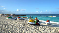 Jet skis on the sandy beach with two afro men - Bahamas, Nassau Stock Footage