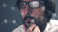 Thinking caucasian businessman looking at infographics on computer monitor. Stock Footage
