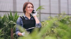 Florist talking on the phone in greenhouse Stock Footage