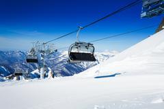 Ski chairlift over mountains on winter resort - stock photo