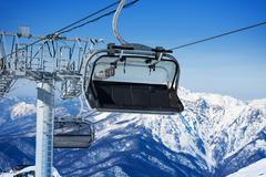 Close view of chairlift and mountains on resort - stock photo