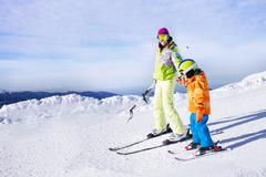 Teaching little boy to ski going holding hand - stock photo