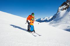 Dad teach little son to ski in mountains - stock photo