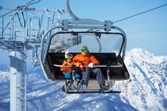 Father and boy sit in ski lift over mountains Stock Photos
