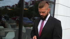 Young bearded businessman using mobile phone outside the office - stock footage