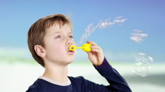 Boy at beach with soap bubbles - stock footage